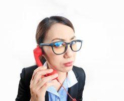 ストレスでイライラしながら電話をする女性社員