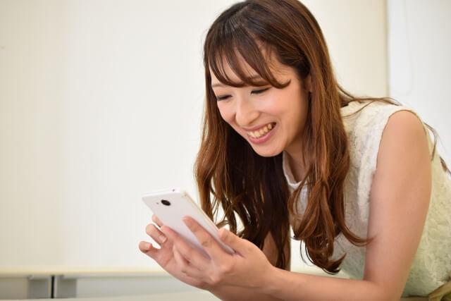 スマホでSNSのアイコン画像を設定する若い女性