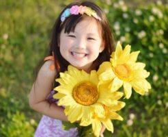 「子ども好きな人」からお花をプレゼントされて喜ぶ笑顔の女の子