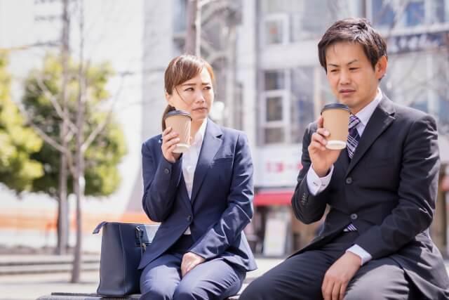 営業先とどう取引するか悩んでいる決断力のない男性社員と女性社員
