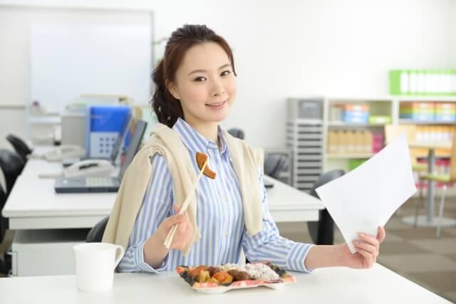 ランチの時間にお弁当を食べながら仕事をするせっかちな女性会社員
