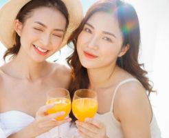 ビーチ沿いの喫茶店でジュースを飲む露出の多い2人の女性