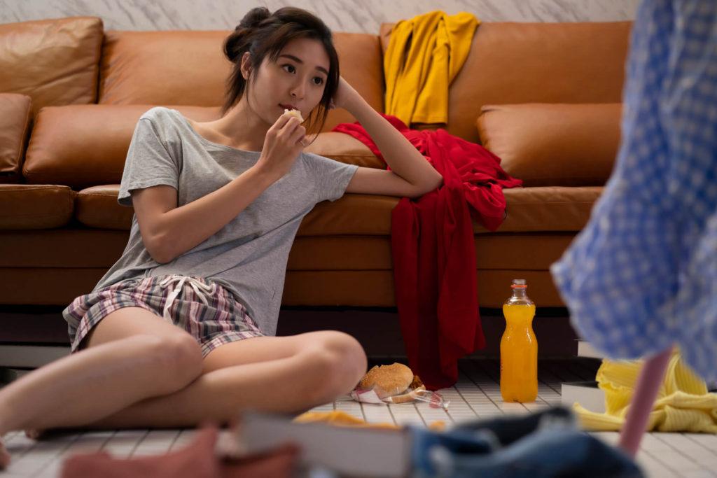 散らかった部屋で直座りし、ハンバーガーを食べながらテレビを見ているだらしない女性