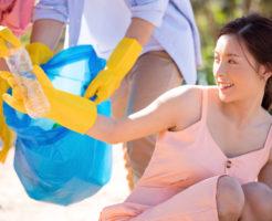 海岸清掃のゴミ拾いに参加しているボランティア好きな女性